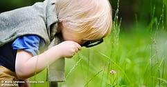 Kind das mit Lupe Blume betrachtet