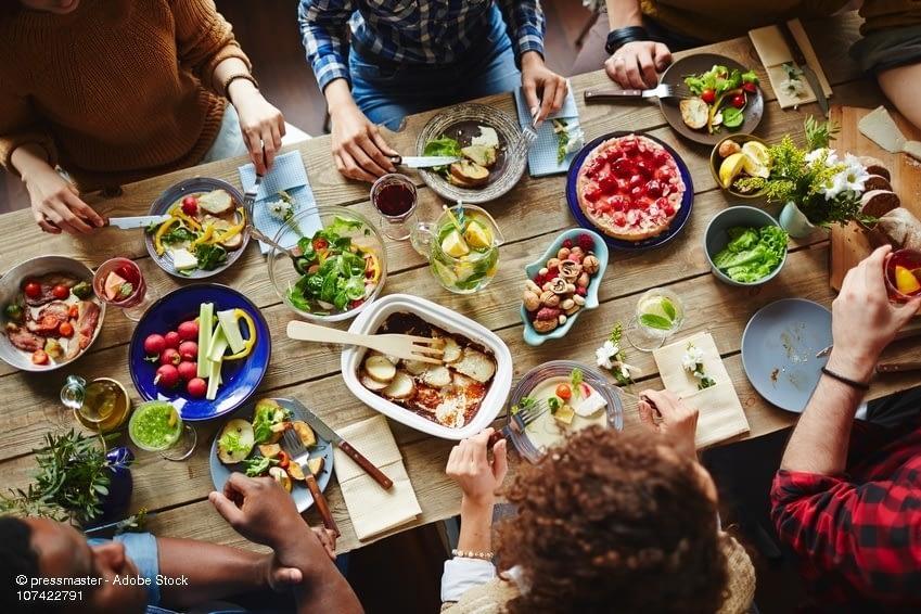 Freunde essen an Tisch ein leckeres Abendessen