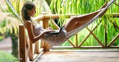 Frau mit Laptop in Hängematte