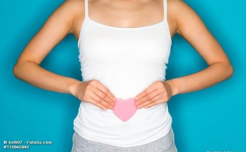 Frau hält Papierherz vor Bauch