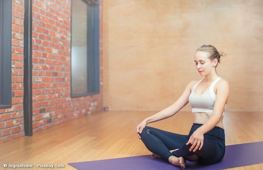 Eine Frau sitzt auf der Yogamatte und meditiert